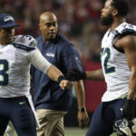 Russell Wilson congratulates Michael Bennett on...